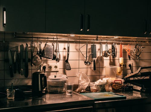 Kitchen counter with cupboards and assorted utensils hanging above table top with dishware teapot and cutting board in dark kitchen
