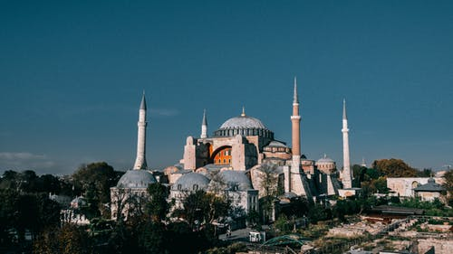 Famous Hagia Sophia grand mosque with high minarets and dome located among green trees in Turkey against blue sky in city