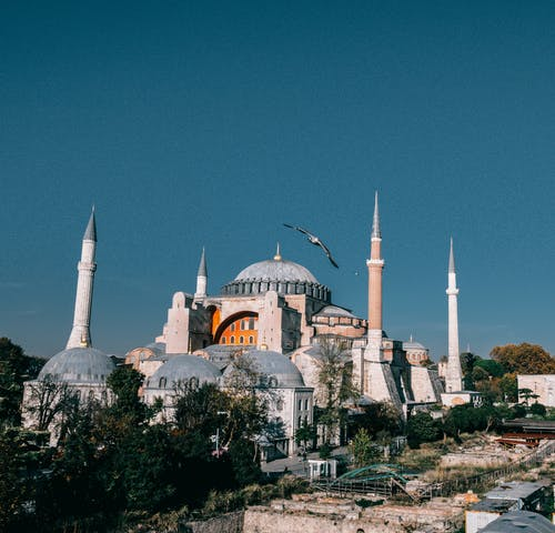 Wonderful Hagia Sophia grand mosque with tall minarets and dome located in Istanbul in Turkey against blue sky in city