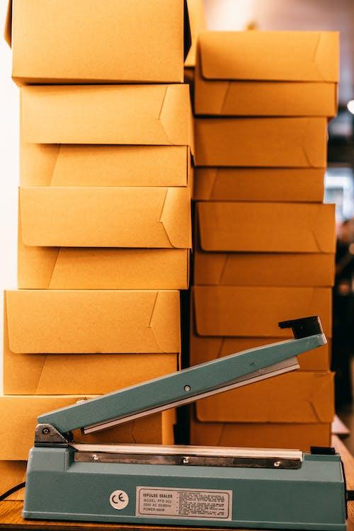 Bag sealer near piles of cardboard boxes in storehouse