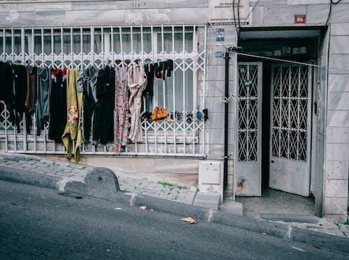Laundry drying on clothesline near condominium entrance