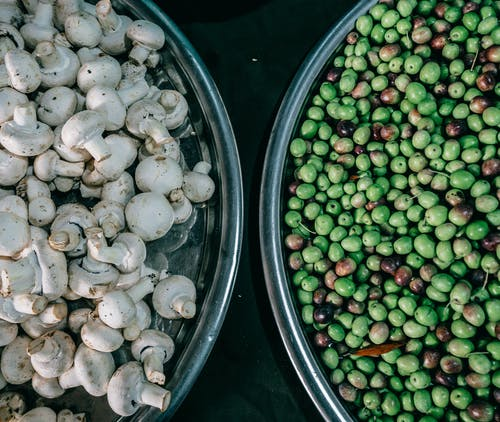Top view composition of ripe raw green peas and fresh mushrooms heaped in steel bowls and placed on dark table