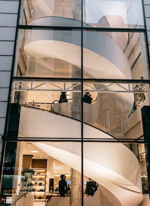 ガラスの壁の前に立っている黒いジャケットの男