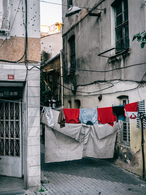 Washed laundry drying on clothesline hanging between old apartment buildings in residential city district
