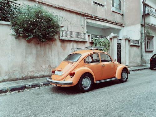 An Orange Volkswagen Beetle Parked on the Street