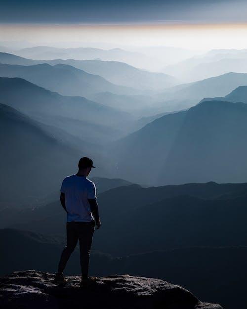 산 위에 서있는 파란색 셔츠에 남자