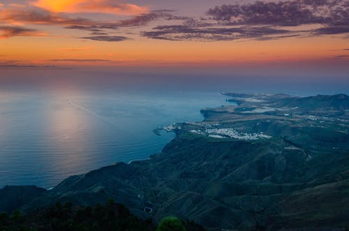Aerial View of Green Mountains and Sea during Sunset
