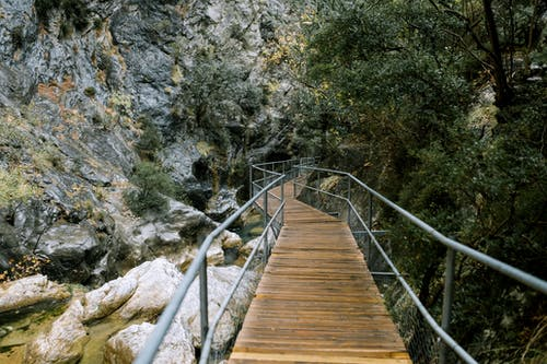 Small footbridge over river in mountainous terrain
