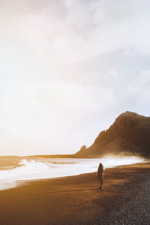 Anonymous distant traveler standing on seashore with rocky cliff while admiring view of stormy sea against cloudy sky in nature