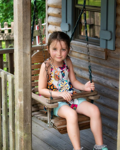 Happy girl smiling while riding on wooden swing of house