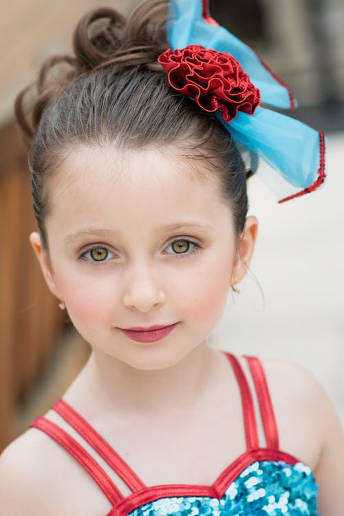 Cute girl with festive hairstyle with bright red bow