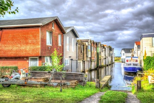 Photo of White and Blue Speedboat Beside Houses
