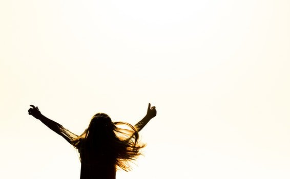 Silhouette of Woman Raising Her Hands