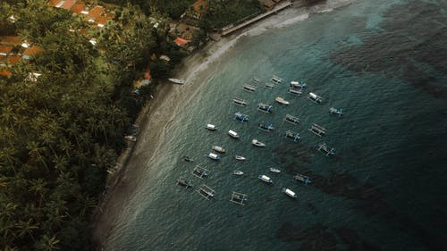 Boats floating on water near coastal village