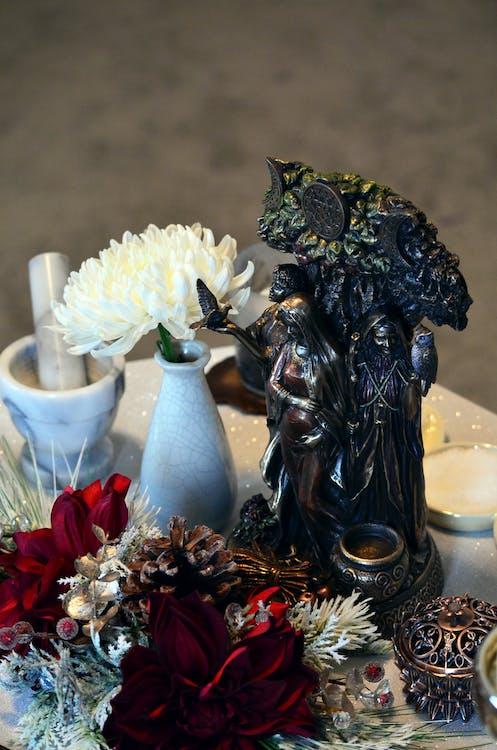 Black Ceramic Figurine on Brown Wooden Table