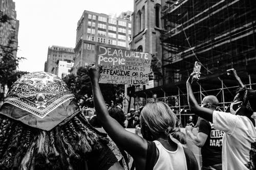 Black and white of anonymous multiracial activists with placards fighting for human rights in city