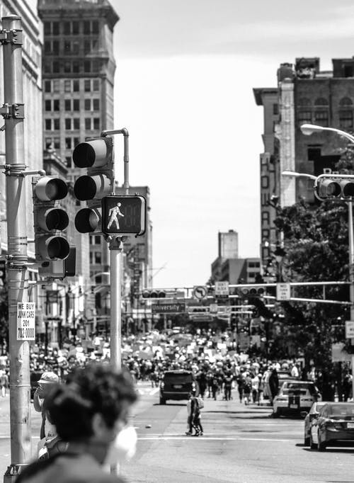 Black and white of anonymous citizens on roadway with traffic light between aged multistage house facades in New York City