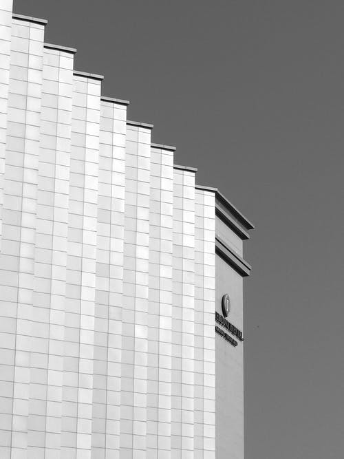 From below black and white of modern geometric architecture construction in street in daytime