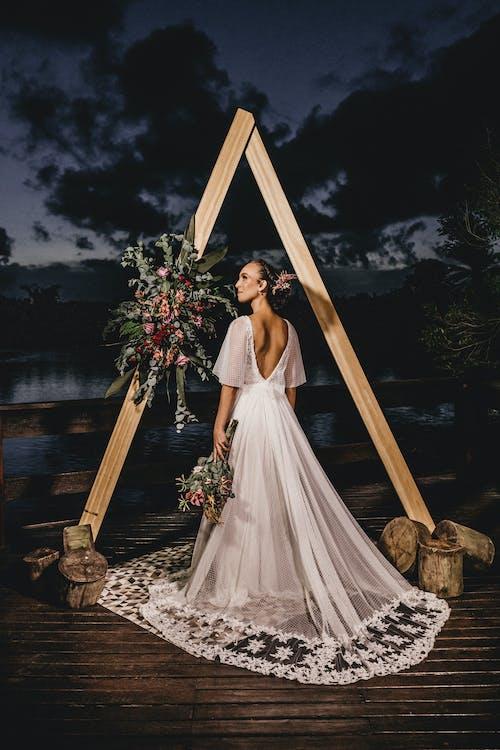 Elegant bride in lace dress on cloudy coastal terrace