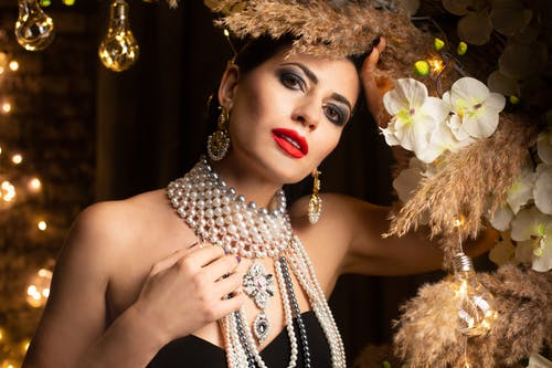 Woman with pearl necklace  standing in room with decorations and looking at camera