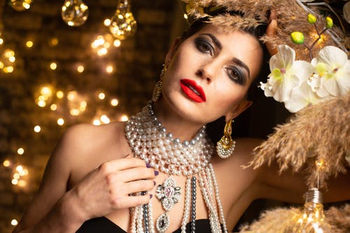 Woman with bright makeup in pearl necklace looking at camera against garlands