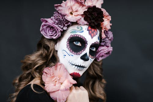 Young female with sugar skull make up and hair decorated with flowers for celebrating Halloween
