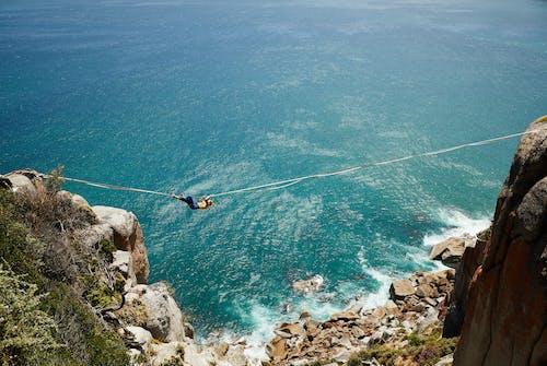 Anonymous woman on zipline over stony coast