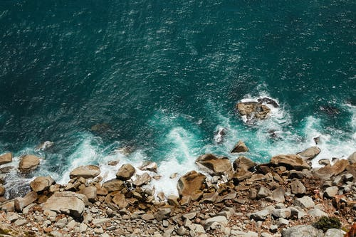 Top view of rocky shore washed with azure foamy rippling water of sea