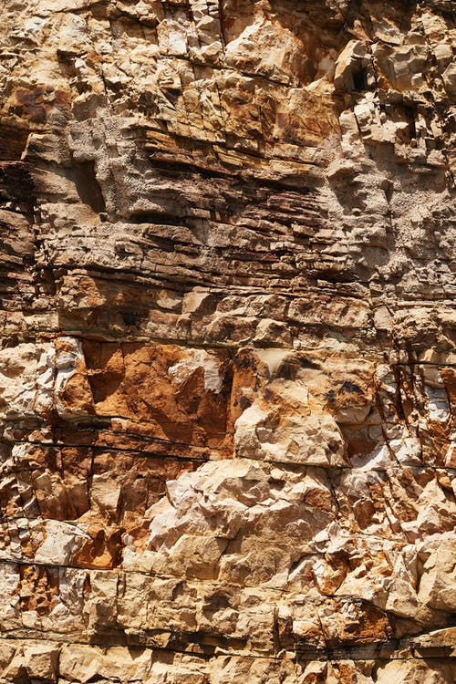 Stony surface of rough rocky formation with dry uneven bristly texture and relief