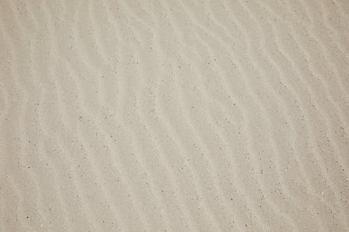 Top view of empty dry plain surface of beach covered with sand in daytime