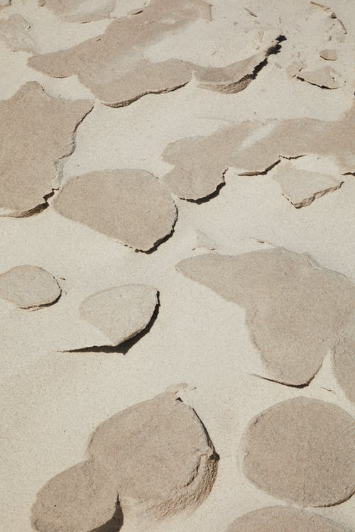From above of ground covered with sand of different textures in desert in daytime