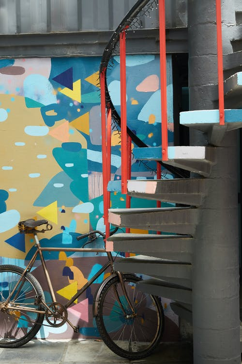Bicycle parked near colorful wall