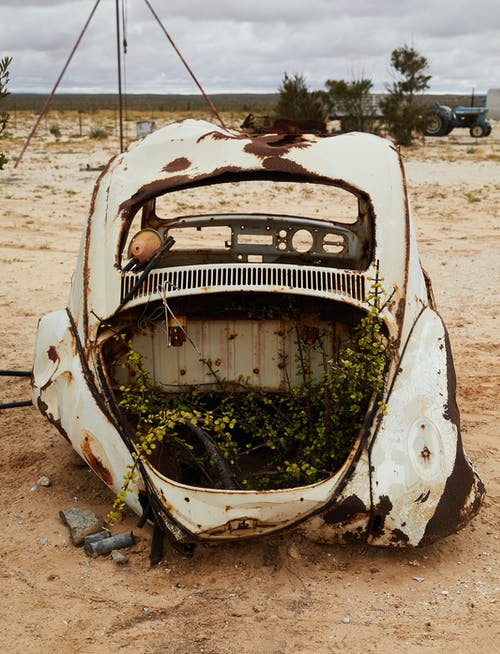 Abandoned broken car in sandy terrain