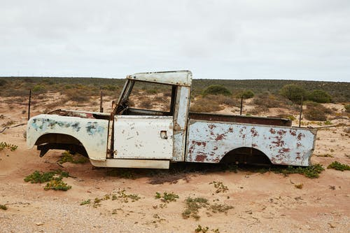 Rusty abandoned car near fence in desert