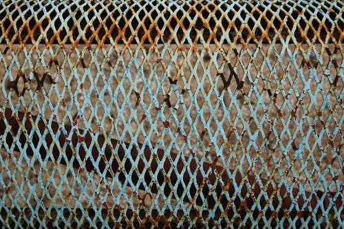 Full frame of weathered blue metal lattice with rusty parts and spots placed on fence in daytime