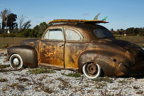 Vintage rusty broken car on gravel