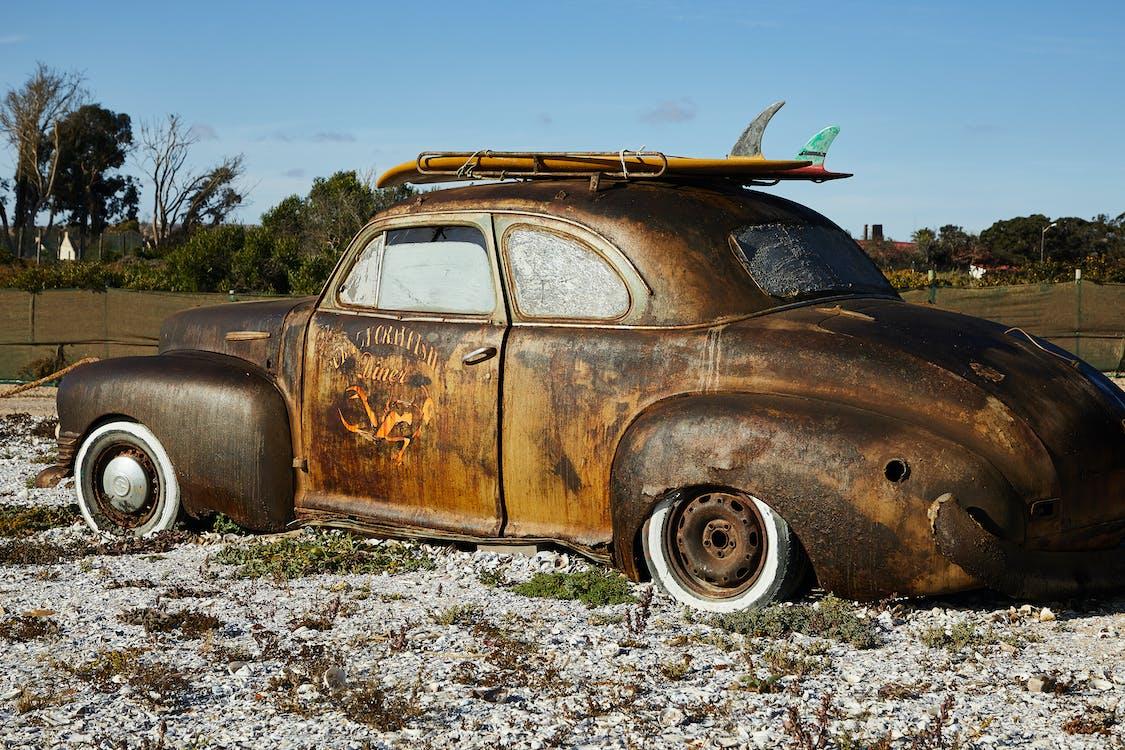 Vintage rusty broken car on gravel