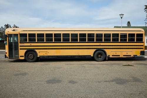 Empty yellow large school bus parked on asphalt road under cloudy blue sky in daytime