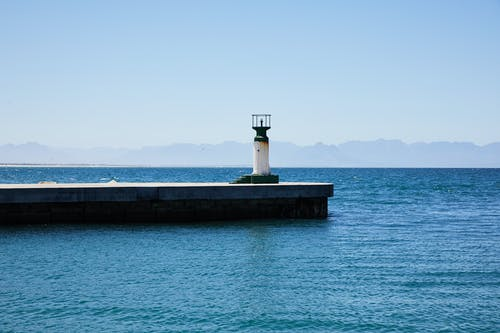 Old lighthouse on pier among rippling water of sea