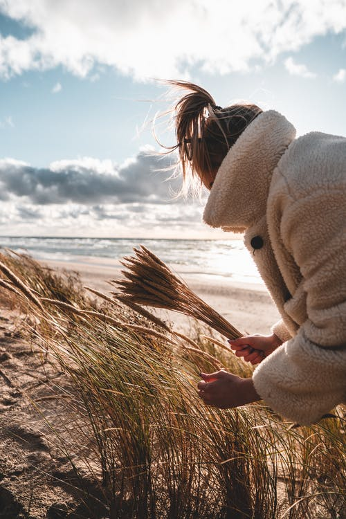 Kobieta W Biały Sweter Stojący Na Brązowej Trawie W Pobliżu Morza