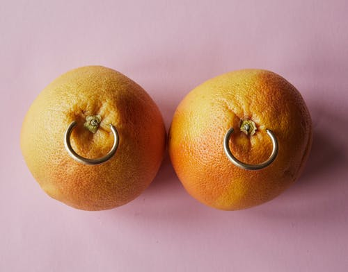 Fresh mandarins with earrings placed on pink surface