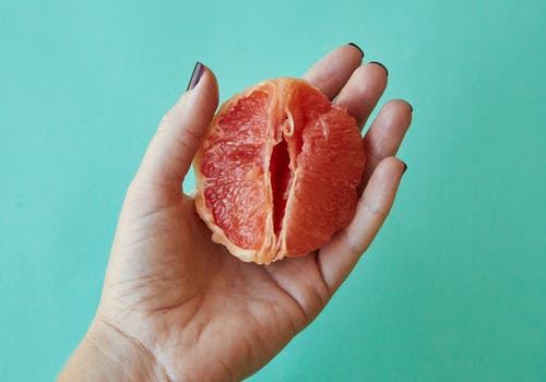 From above of crop anonymous female demonstrating half of juicy peeled grapefruit as vagina against blue background in studio