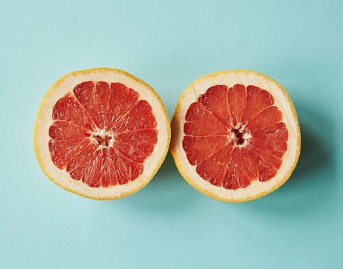 From above of halves of bright orange juicy grapefruit placed on light blue background in studio