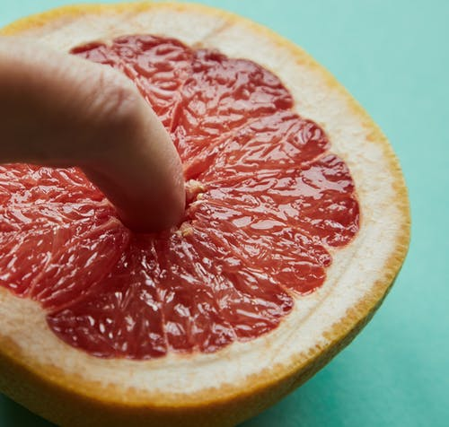 From above of crop anonymous person sticking finger in half of fresh juicy grapefruit against light green background