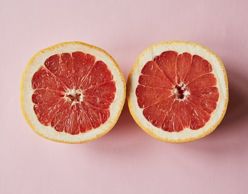 Top view of fresh sliced juicy grapefruit placed on pink background in studio