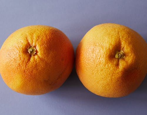 From above pair of ripe juicy oranges placed on light purple background in studio