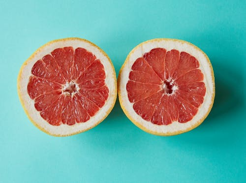 Ripe sliced grapefruit placed on blue surface