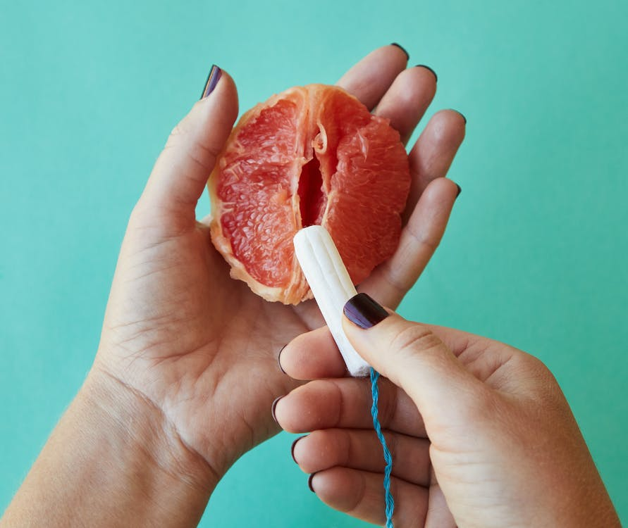 From above of crop anonymous female demonstrating on sliced ripe grapefruit correct use of tampon against blue background