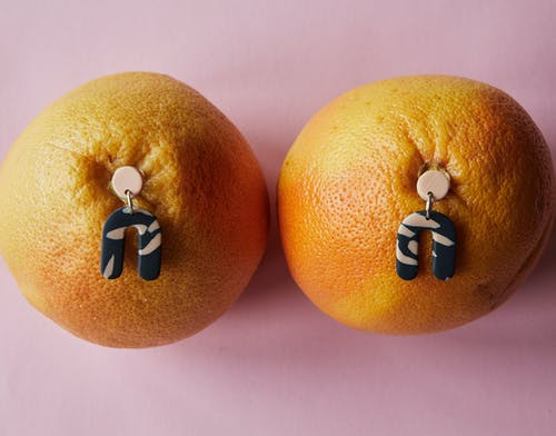 Top view of trendy earrings stucking in fresh ripe tangerines placed on pink surface in studio