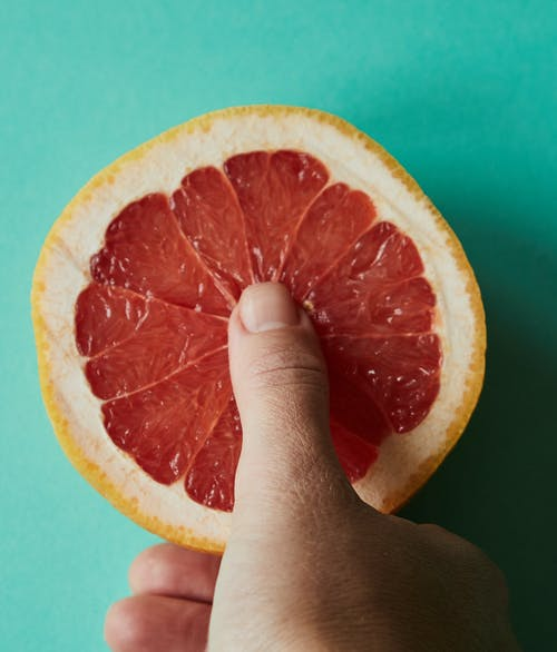 Person touching ripe grapefruit against light green background
